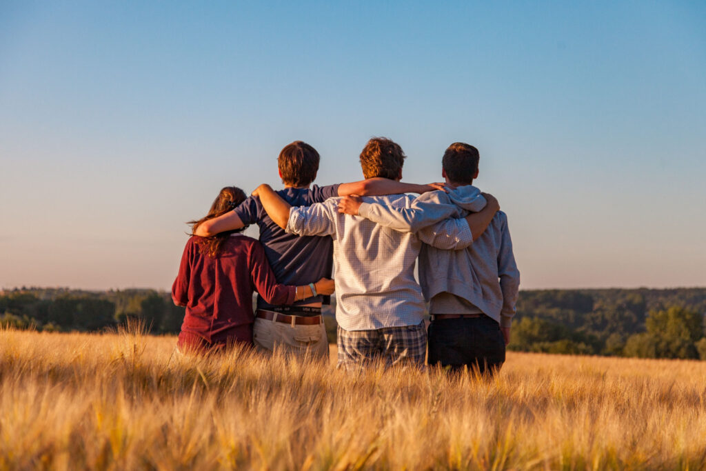 An image of a group of friends, their backs toward the viewer, arms around each other's shoulders, standing in a wheat field and looking at a vista.