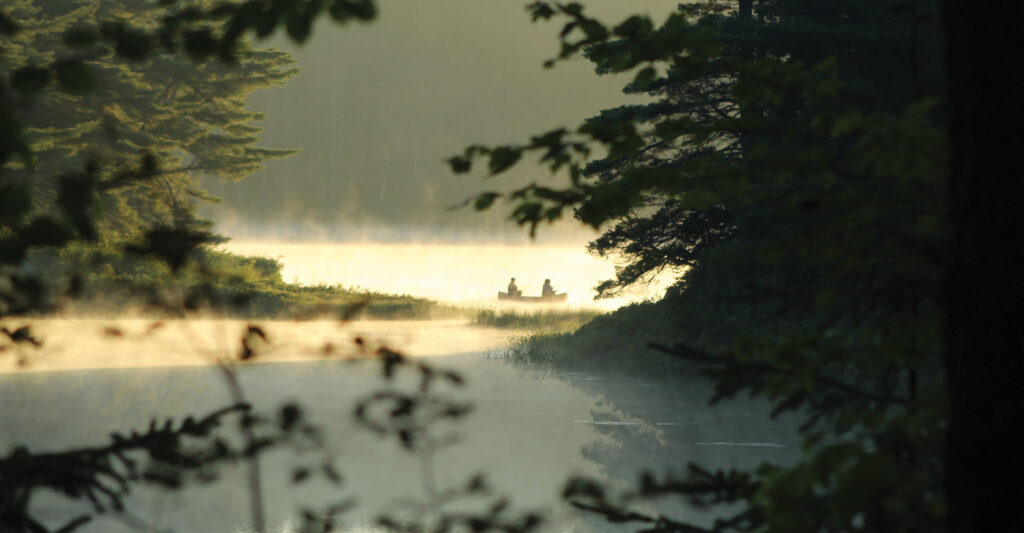 Image of two people in a canoe on a misty lake, viewed from within a forest. Photo by Simone Wessels Bloom.